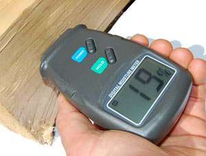 taking a moisture reading of firewood with a moisture meter